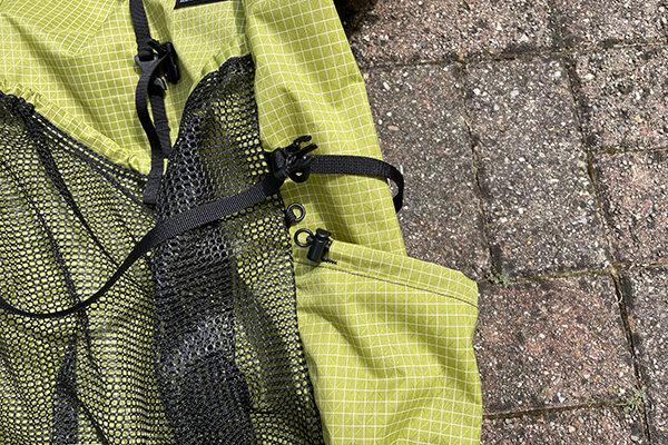 Cinch strap for side pocket on pack